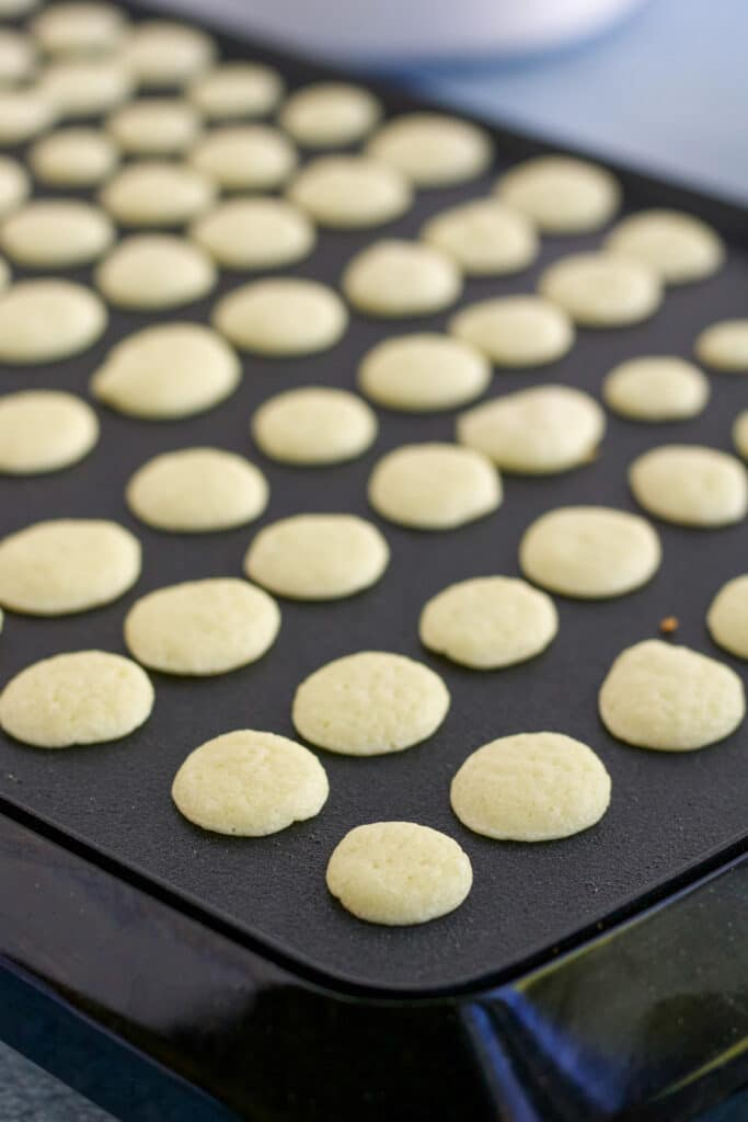 Mini pancakes being cooked on a griddle to make a pancake cereal recipe