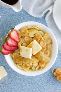 An overhead image of a bowl of pancake cereal in a white bowl with butter and strawberries.