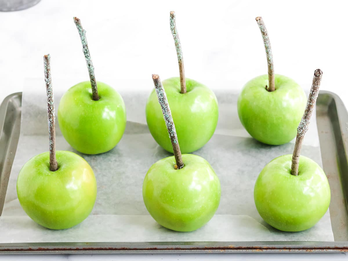 Apples with sticks on a wax lined baking sheet