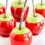 Bright red candy apples on a white marble styling board with glitter topped sticks on top.