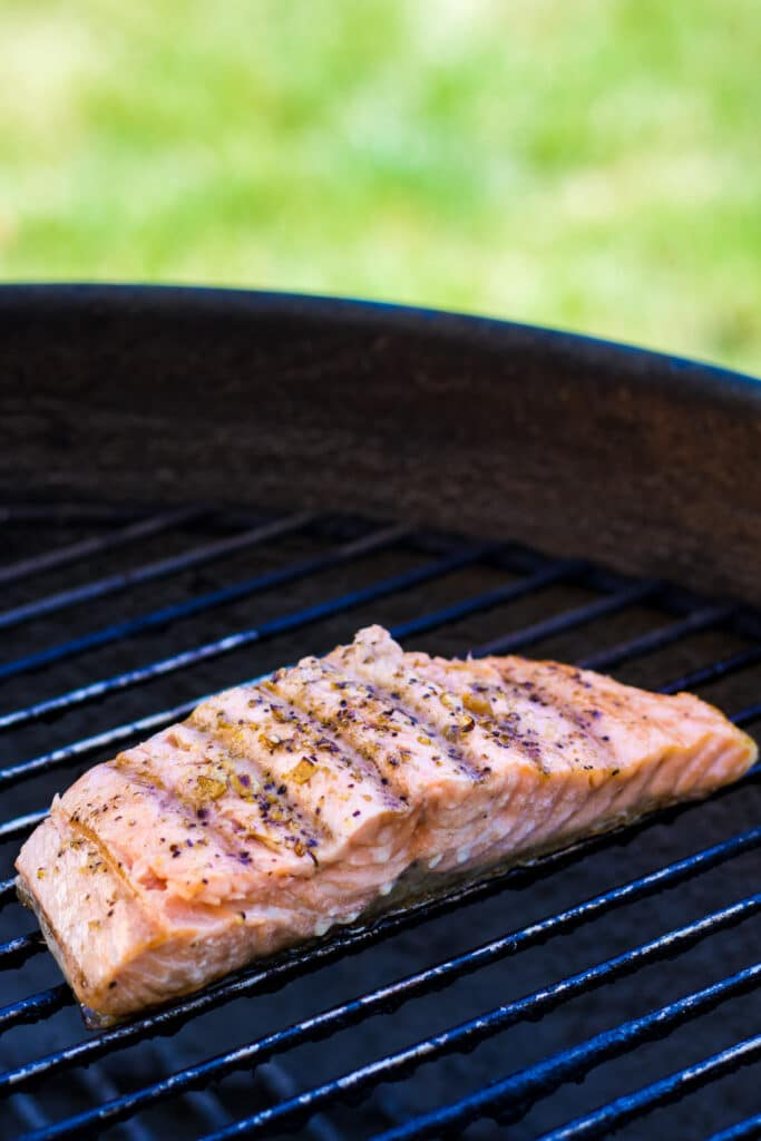 A salmon filet on the grill with seasonings and nice charred grill marks.