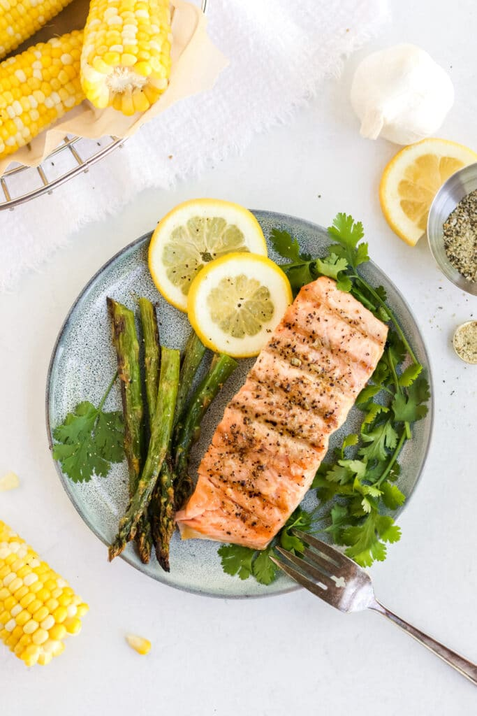 Salmon filet on a plate with herbs, asparagus and lemon, corn on the cob is off in the corner.