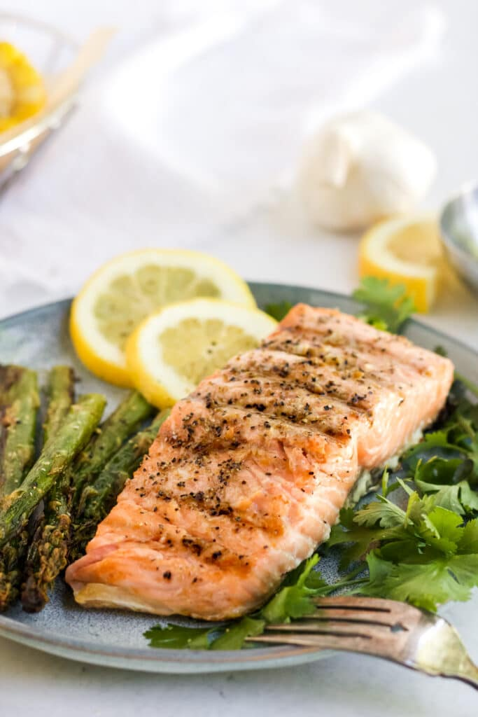 Grilled salmon on a grey plate with herbs and sliced lemons.
