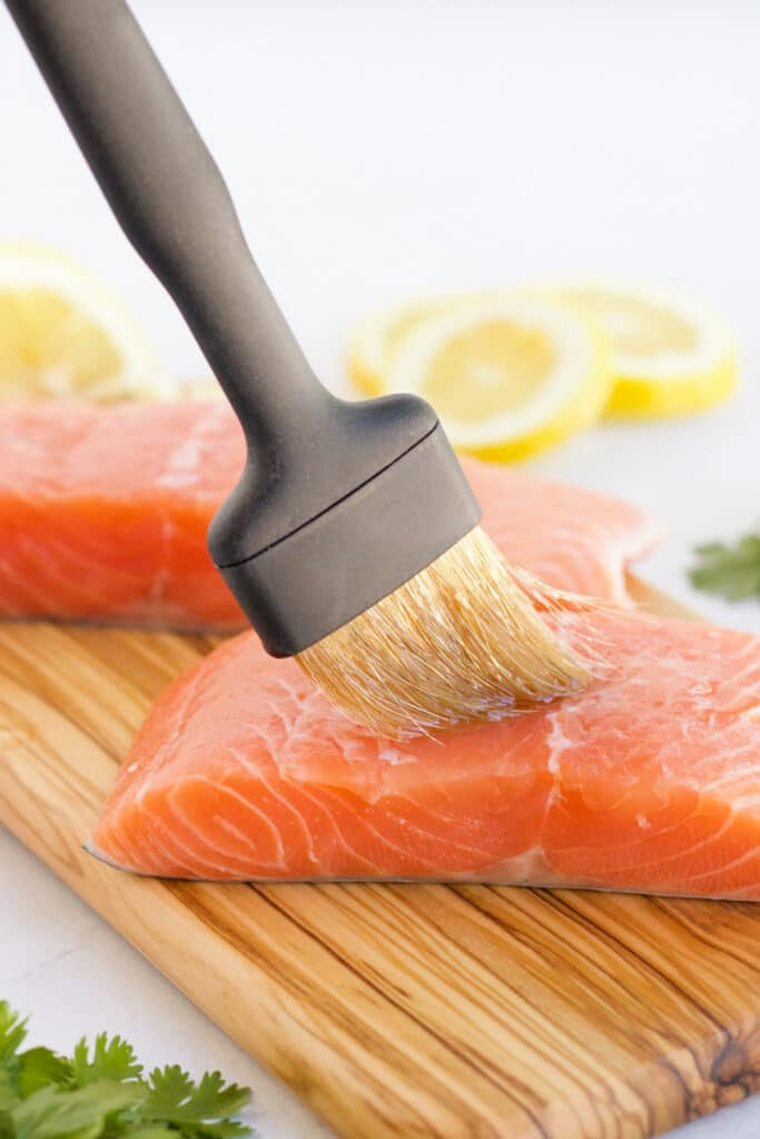 Salmon being prepared for the grill by brushing olive oil on it