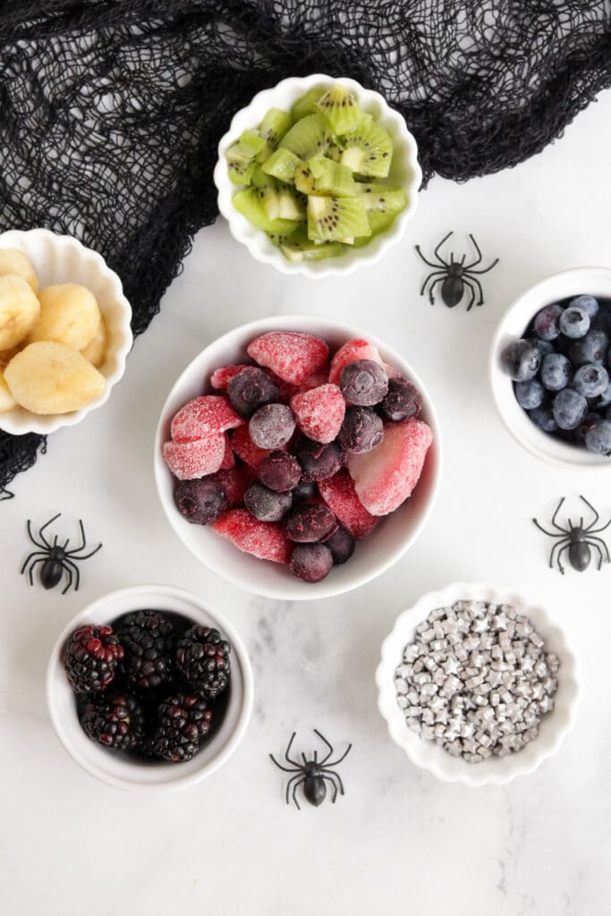 Ingredients to make Halloween Smoothie Bowls - there are little bowls of frozen berries, fresh berries and star sprinkles.