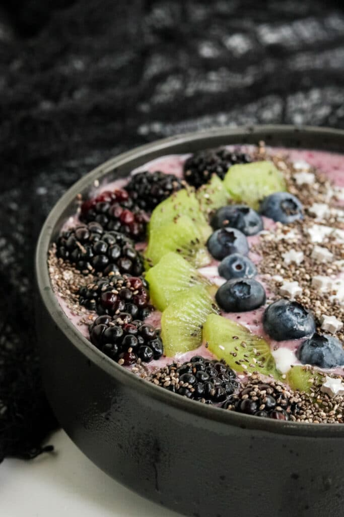 A picture of the side of a Halloween Smoothie Recipe with blackberries, kiwi, blueberries and chia seeds.