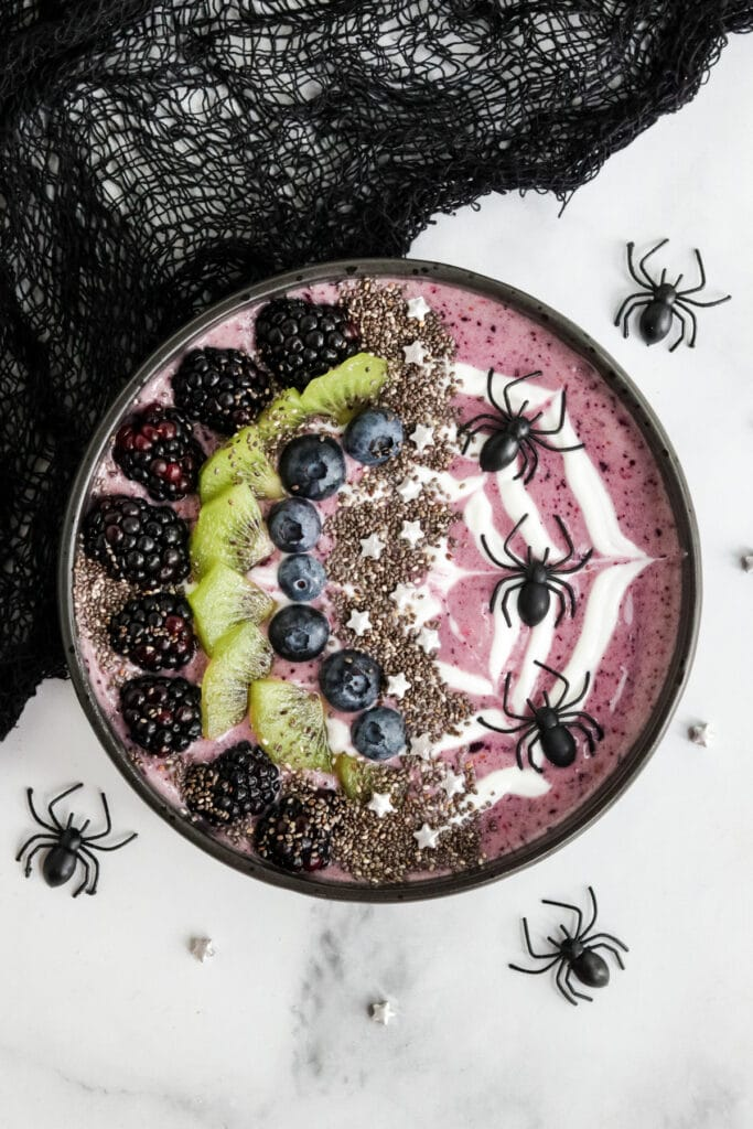 Image of a purple halloween themed smoothie bowl with plastic spiders and a web piped with yogurt