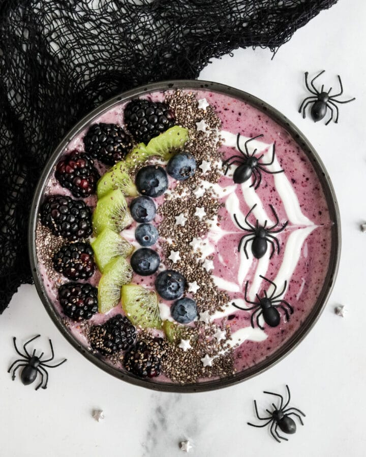 A Halloween Smoothie bowl with a greek yogurt spider web and plastic spiders for decoration.