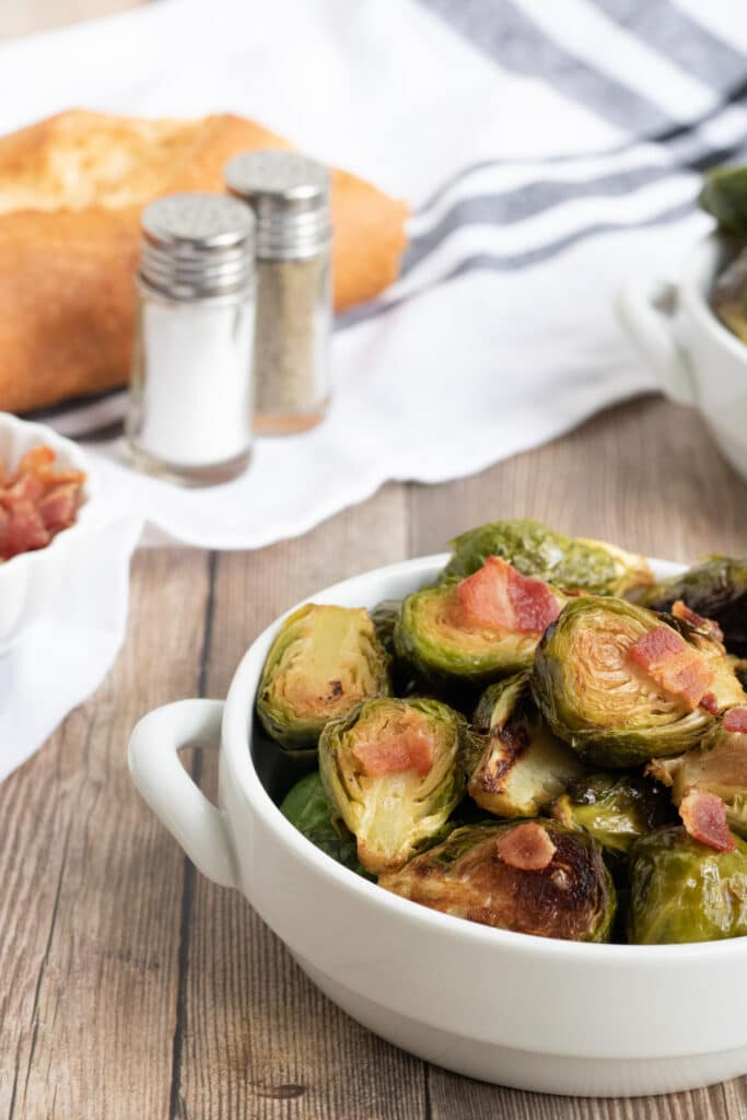 Keto Brussel Sprouts in a white dish on a wooden styling board with bacon on top.