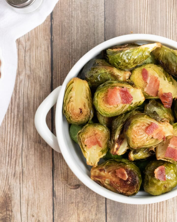 Keto Brussel Sprouts with bacon in a white bowl with a wooden background.