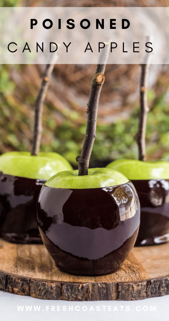 Pinterest Image of Poisoned Candy Apples. Black candy coated granny smith apples with sticks on a wooden serving platter.
