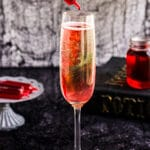 A image of a Halloween Mimosa with a syringe of cherry grenadine.