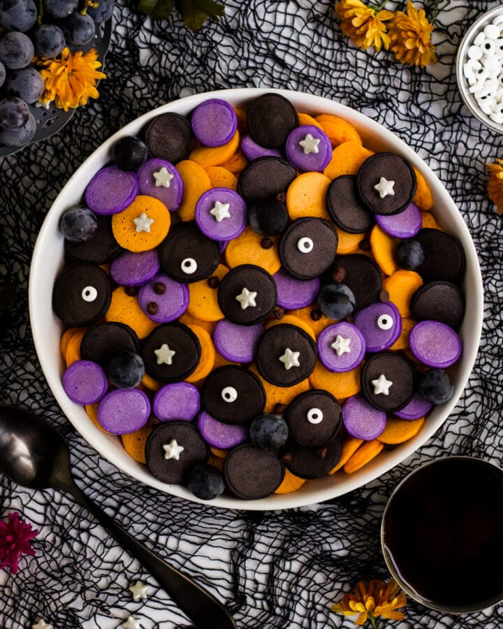 A bowl of purple, orange and black mini Halloween pancakes with candy eyes and stars.
