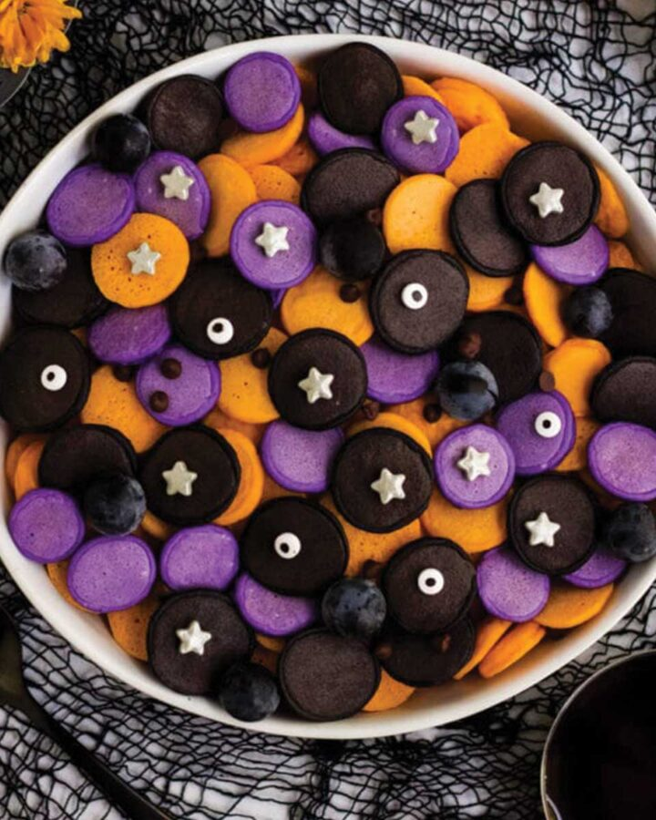 Bowl of mini colored pancakes for halloween pancake cereal.