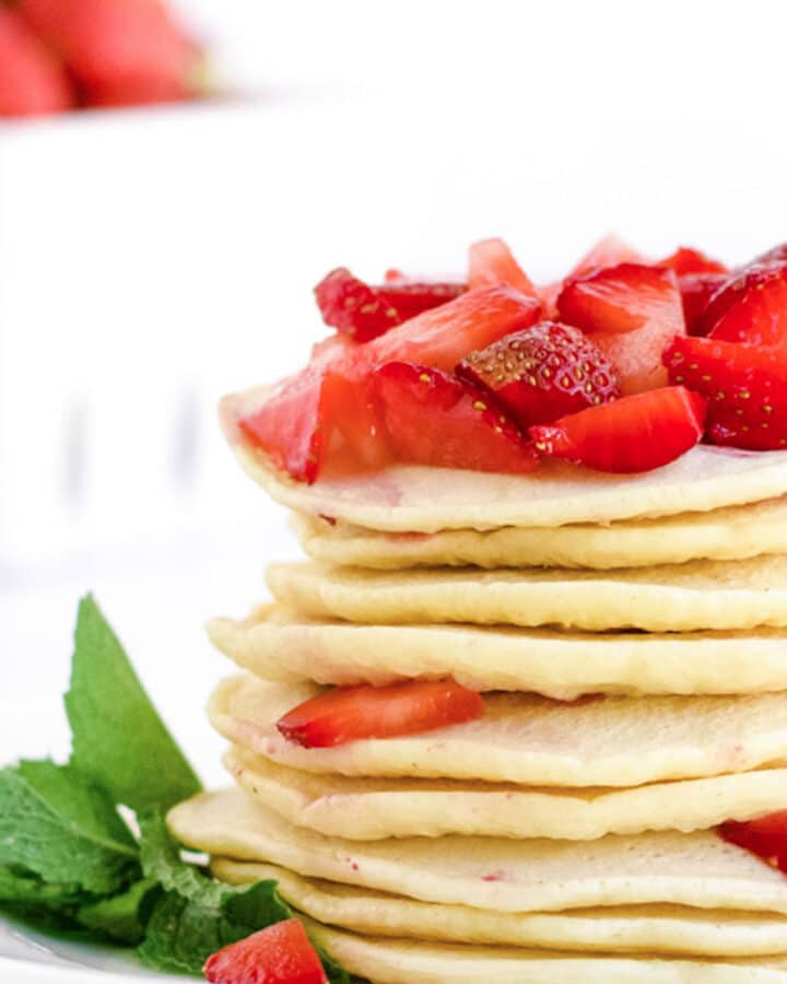 A stack of strawberry pancakes with fresh strawberries on top.