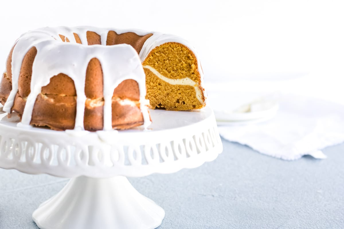 A cream cheese stuffed pumpkin pound cake with a glaze dripping off the sides.