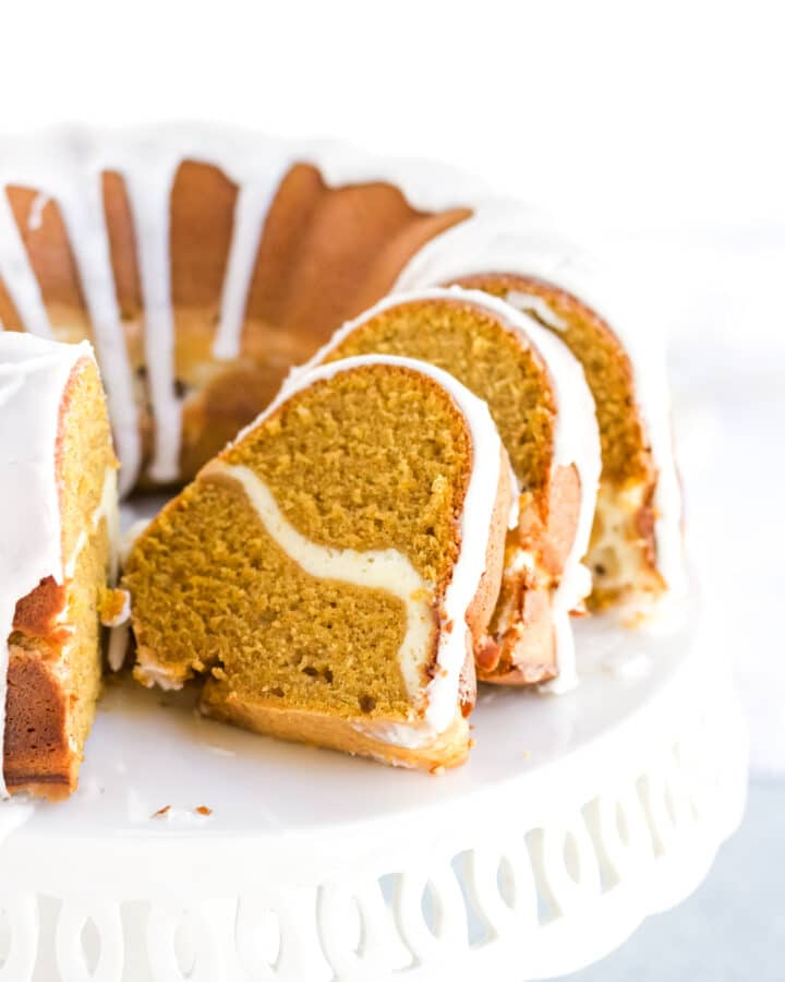 A pumpkin cream cheese pound cake sliced open on a white cake stand.