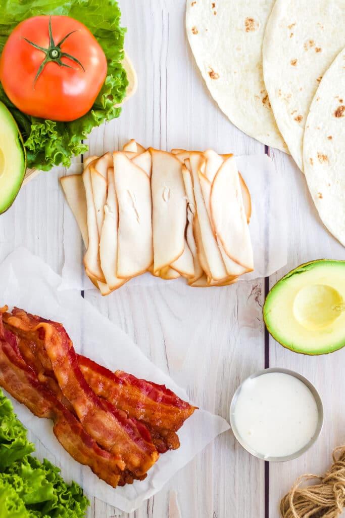 Ingredients to make a turkey bacon BLT wrap.