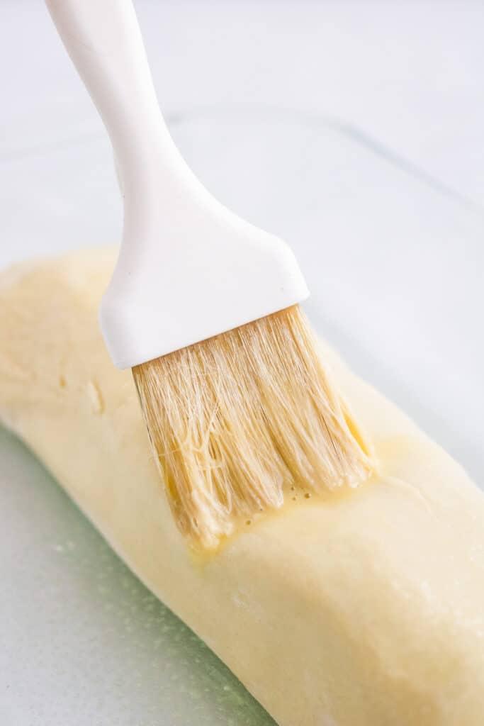 brushing egg wash onto pork wellington