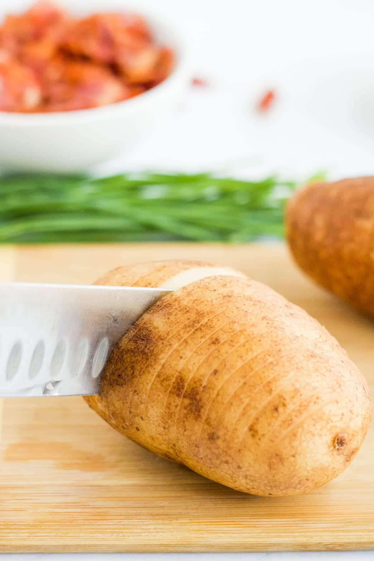 A potato being sliced on a cutting board to make Hasselback Potatoes.