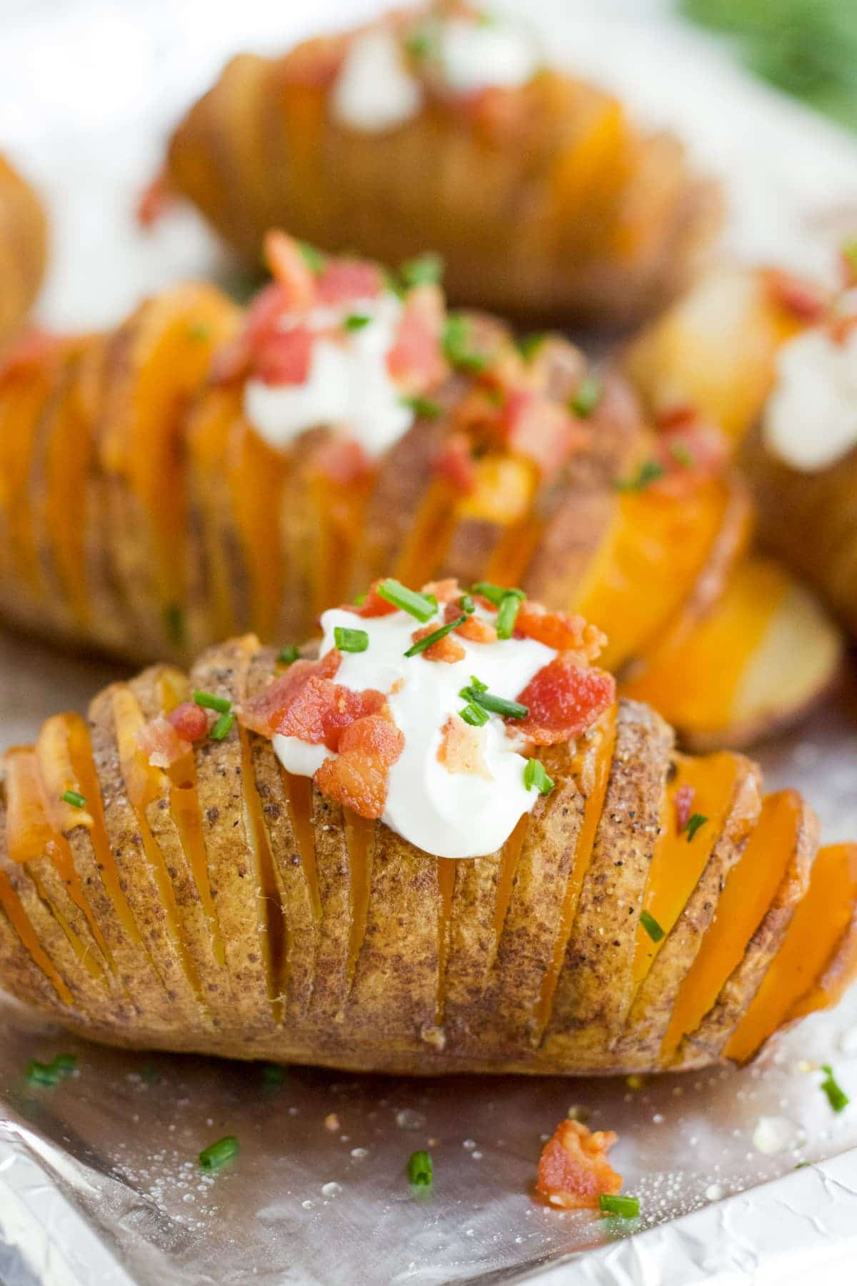 A close up image of a Hasselback potato with sour cream, bacon and chives.