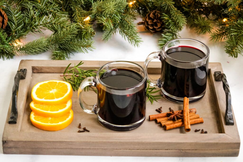 two glasses of mulled wine on a serving tray with orange slices and cinnamon sticks