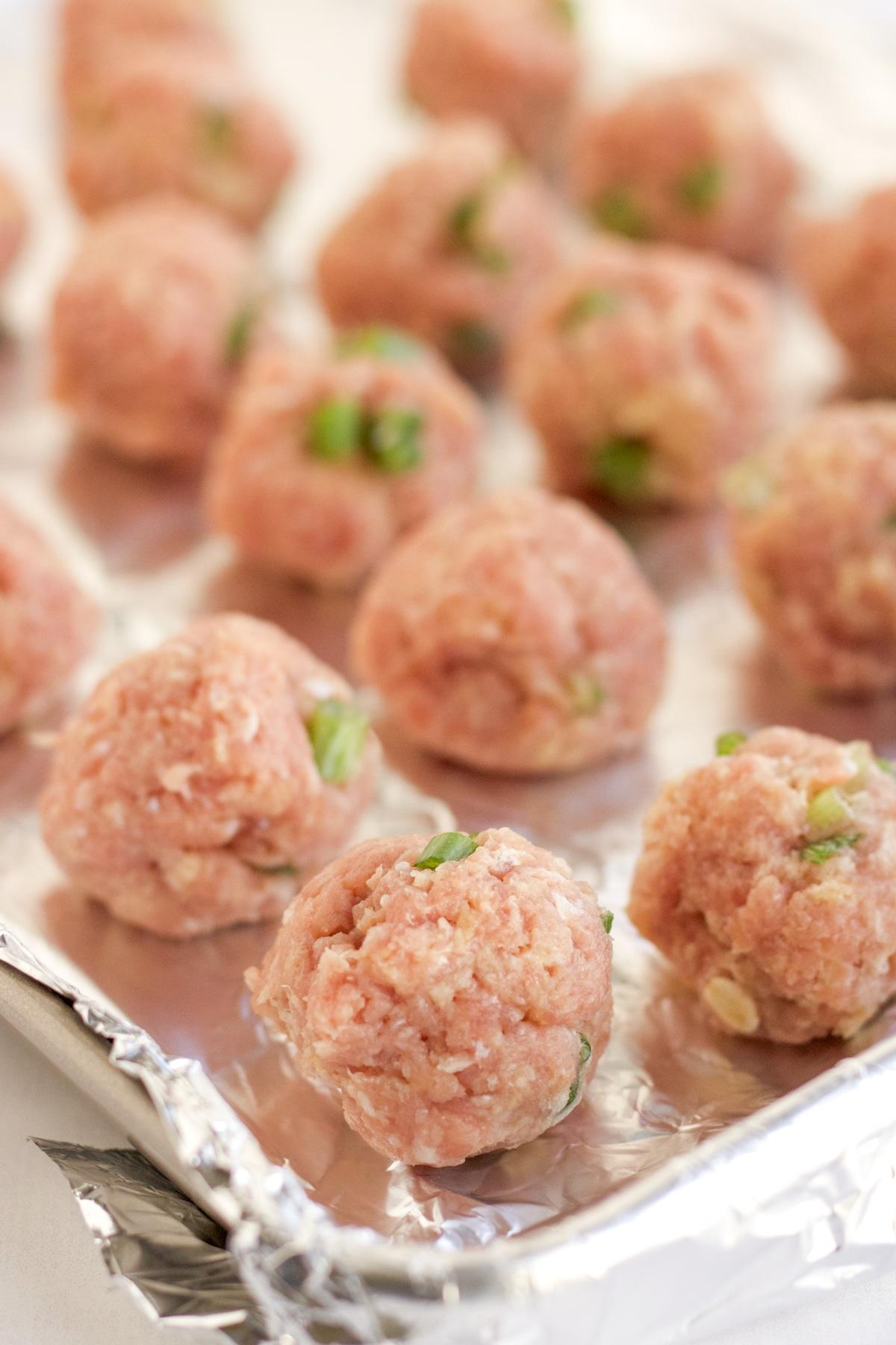 raw meatballs on a foil lined baking sheet