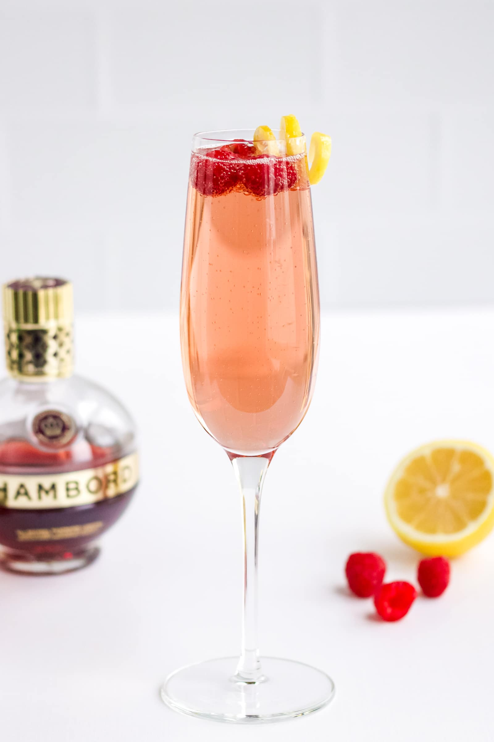 A glass of Chambord and Champagne with a lemon twist and three fresh raspberries on top.