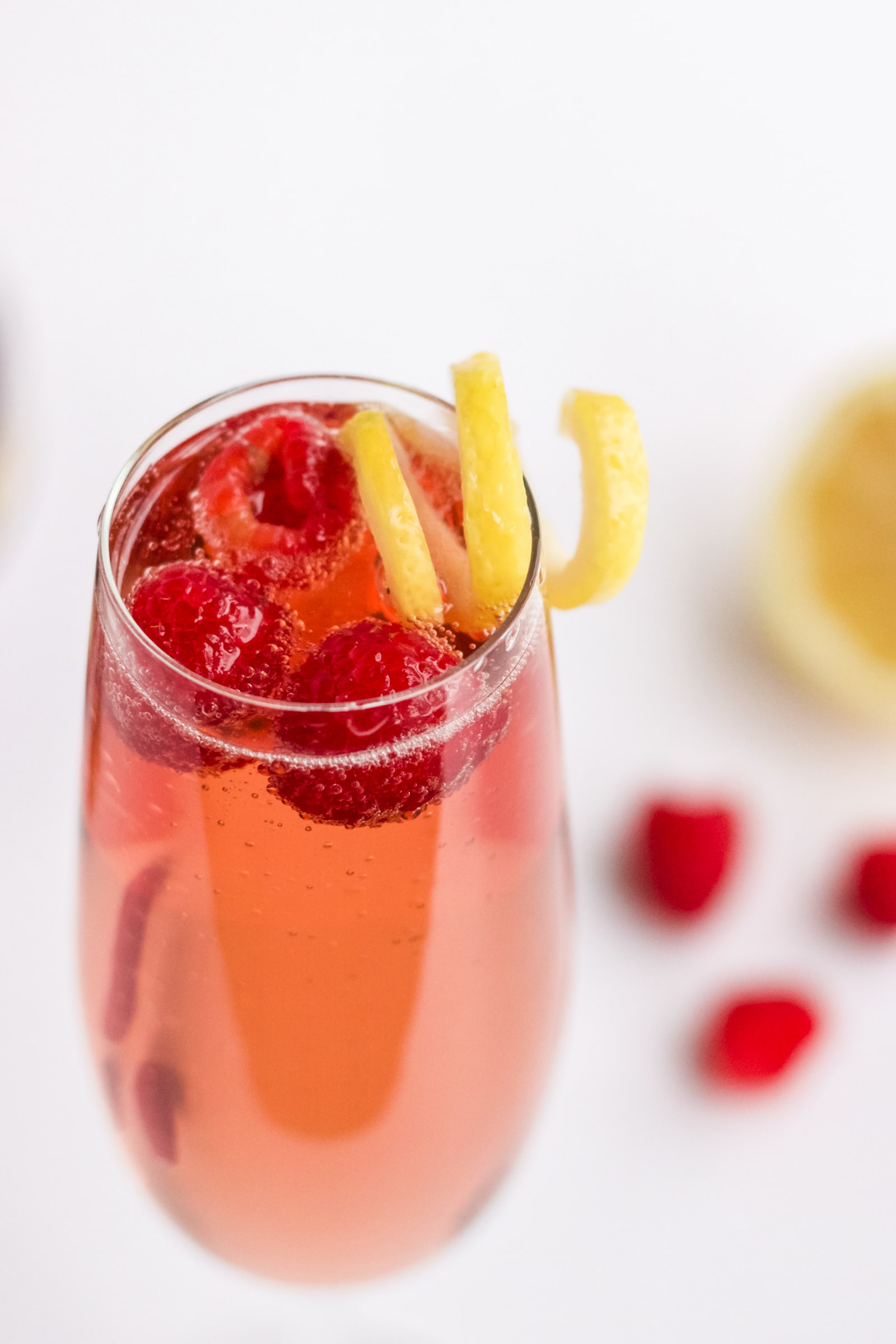 A close up image of chambord and champagne garnished with lemon twist and three raspberries.
