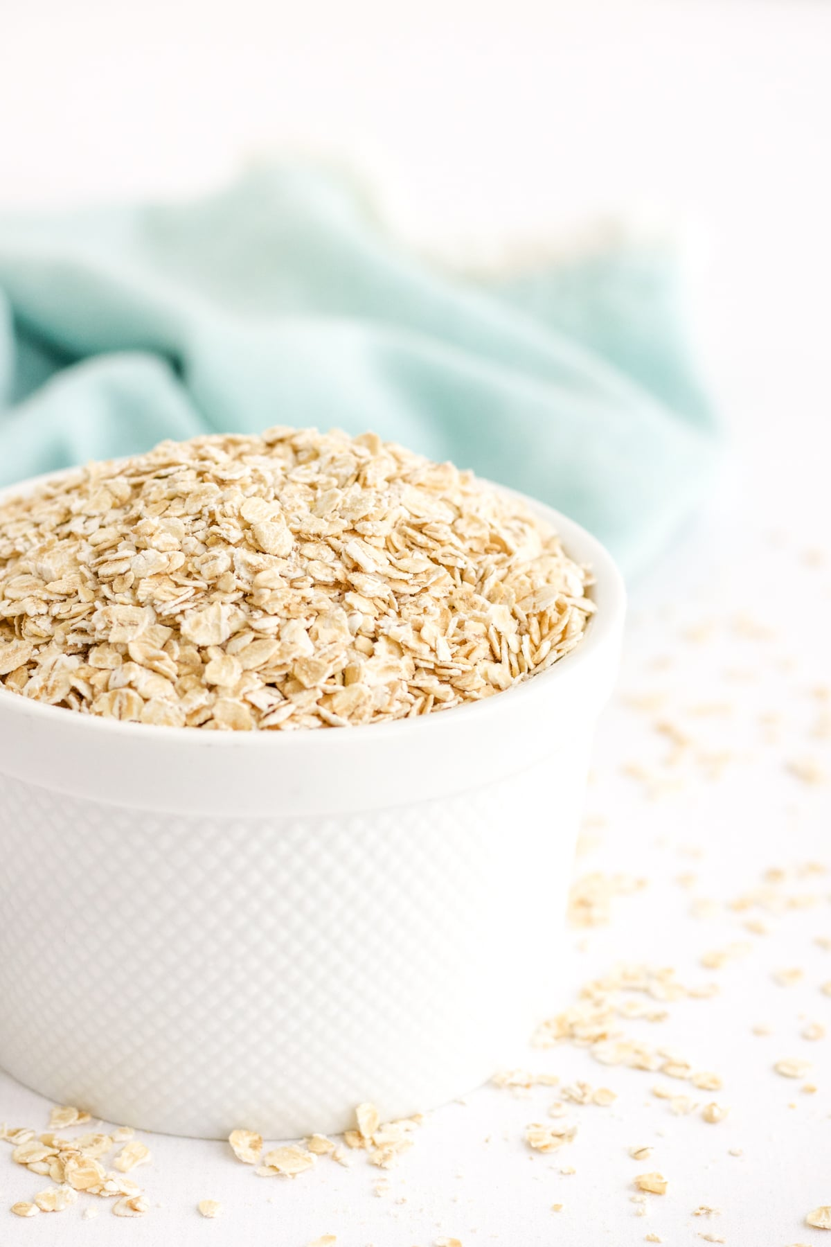 Rolled oats in a white bowl with a teal linen in the back to show how to make oat flour at home.