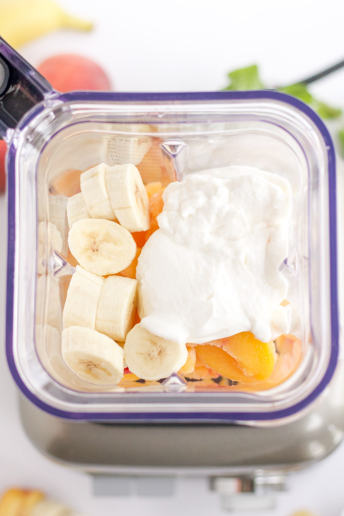 overhead shot of ingredients in a blender: bananas, yogurt and peaches