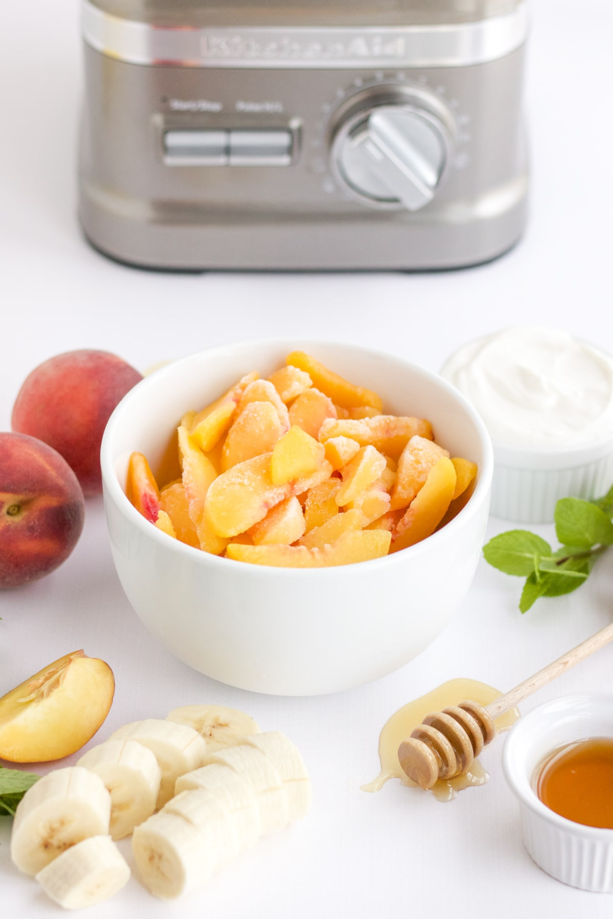 frozen peaches in a white bowl with a bananas, honey and yogurt