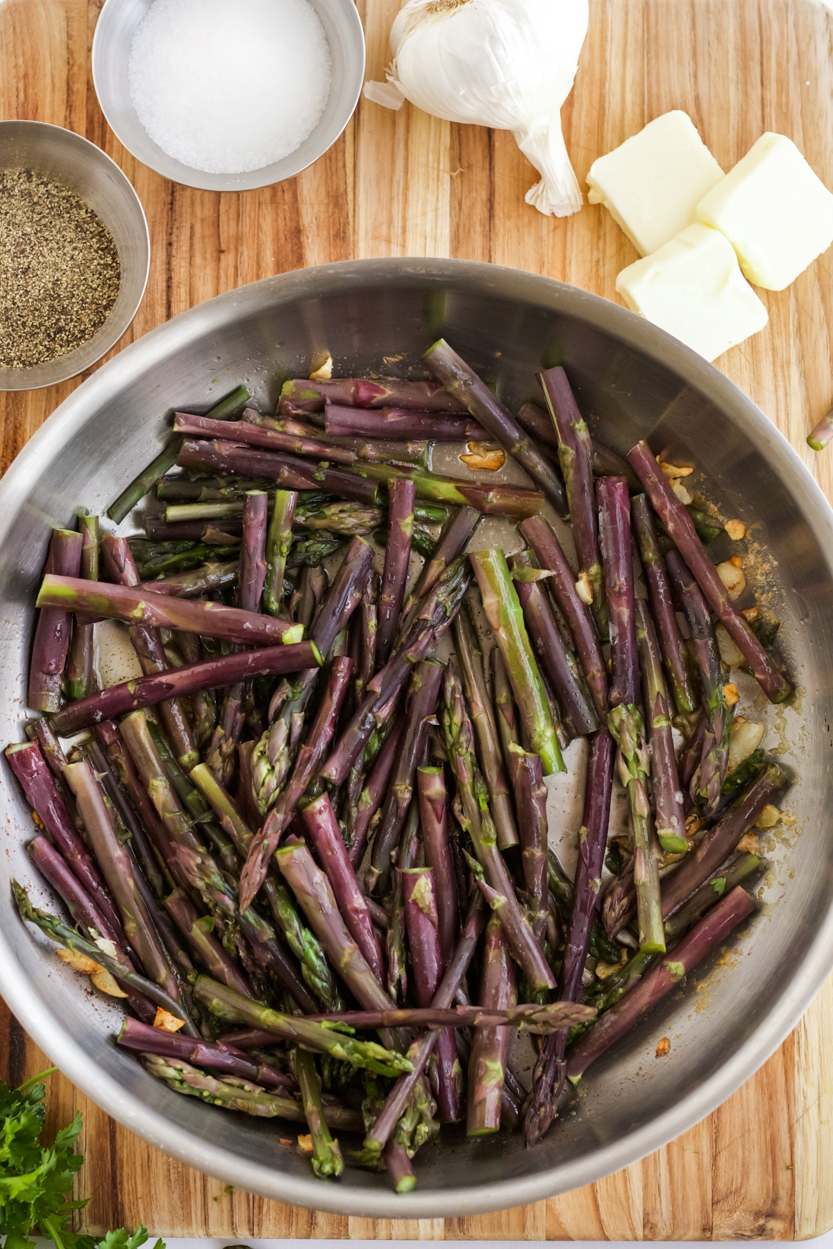 purple asparagus stalks in a skillet on a wooden board with other ingredients