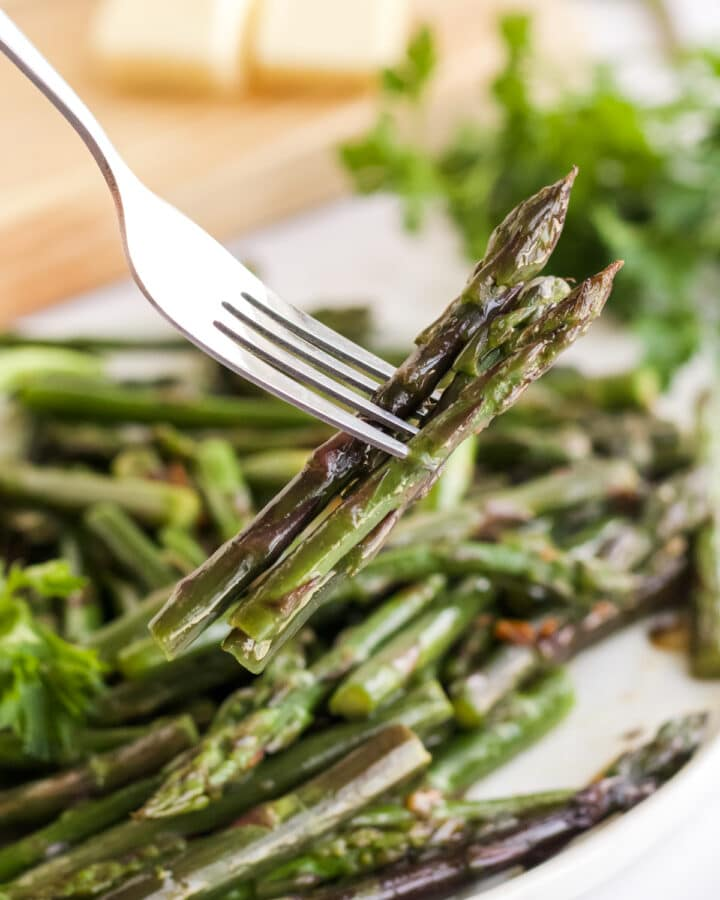 fork holding bites of asparagus from a white plate