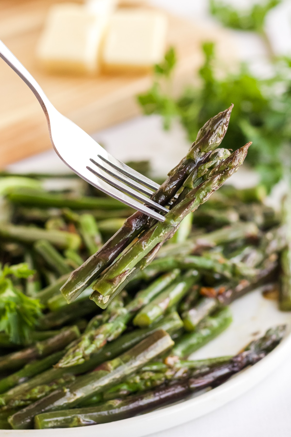 fork holding bites of purple asparagus from a white plate