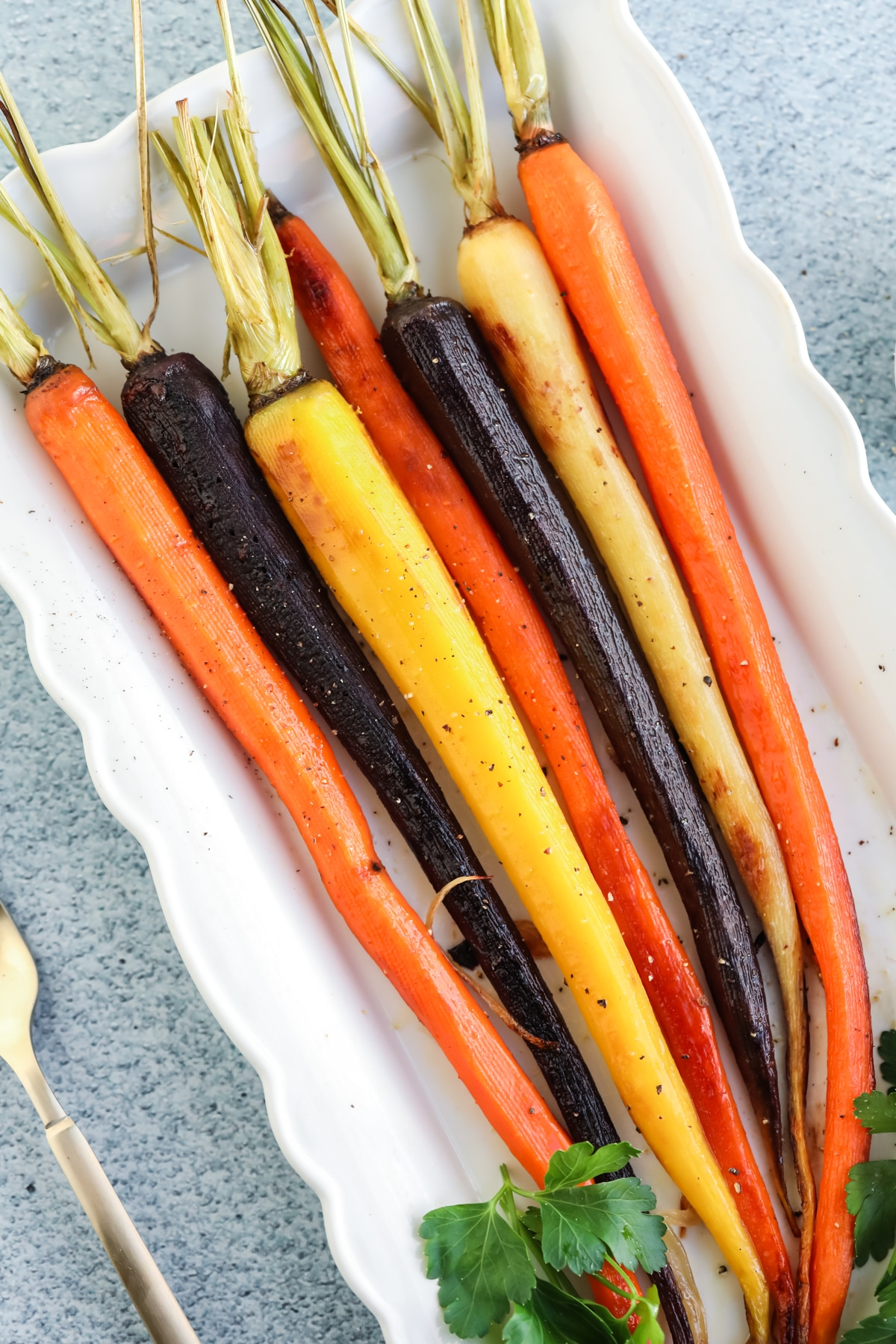 Overhead image of roasted rainbow carrots on a white platter.