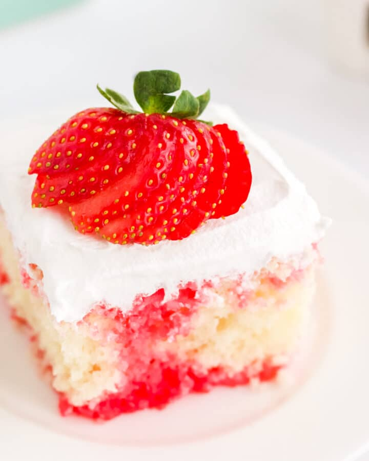 a square slice of white cake with strawberry filling on a white place topped with a strawberry