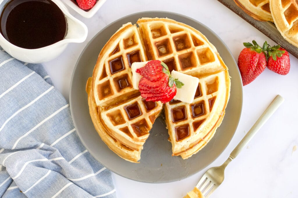 two belgian waffles stacked on a plate topped with strawberries