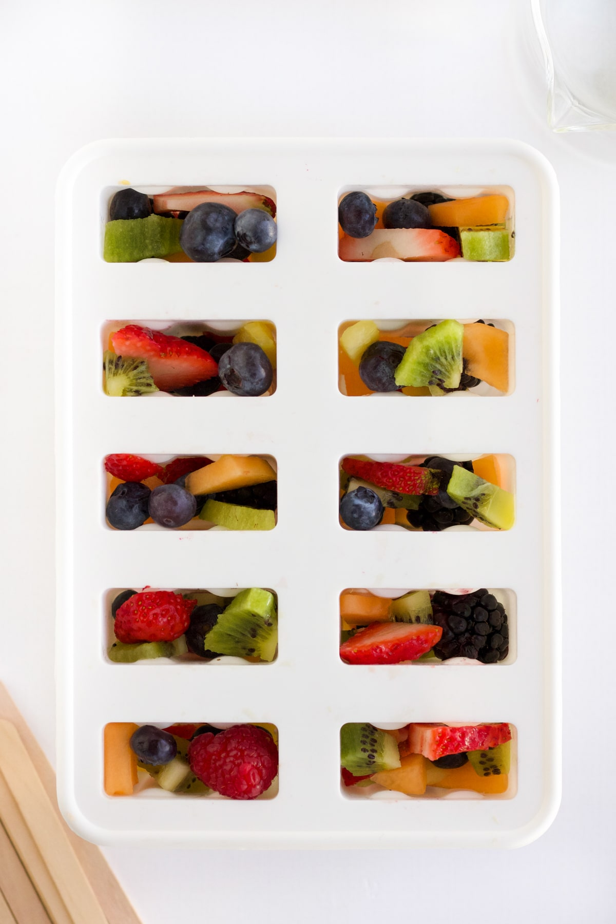 overhead shot of fruit popsicles ready to go in the freezer