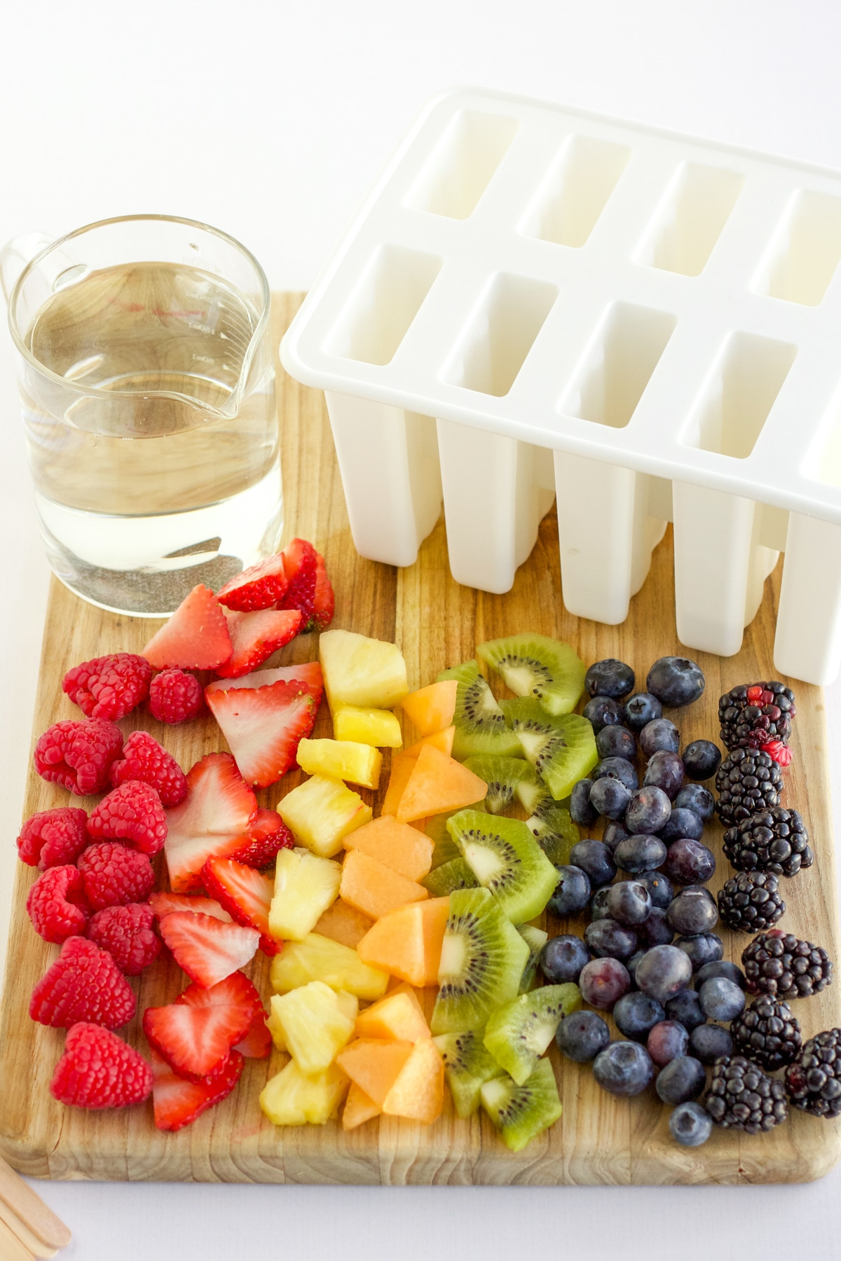 rainbow colored cut fruit on a cutting board with a glass of clear juice and a popsicle mold