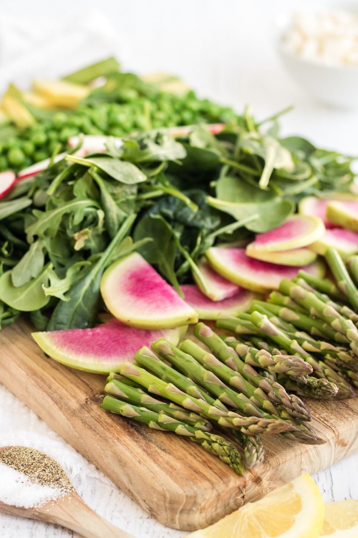 ingredients for spring salad including asparagus and radish on a wooden cutting board.