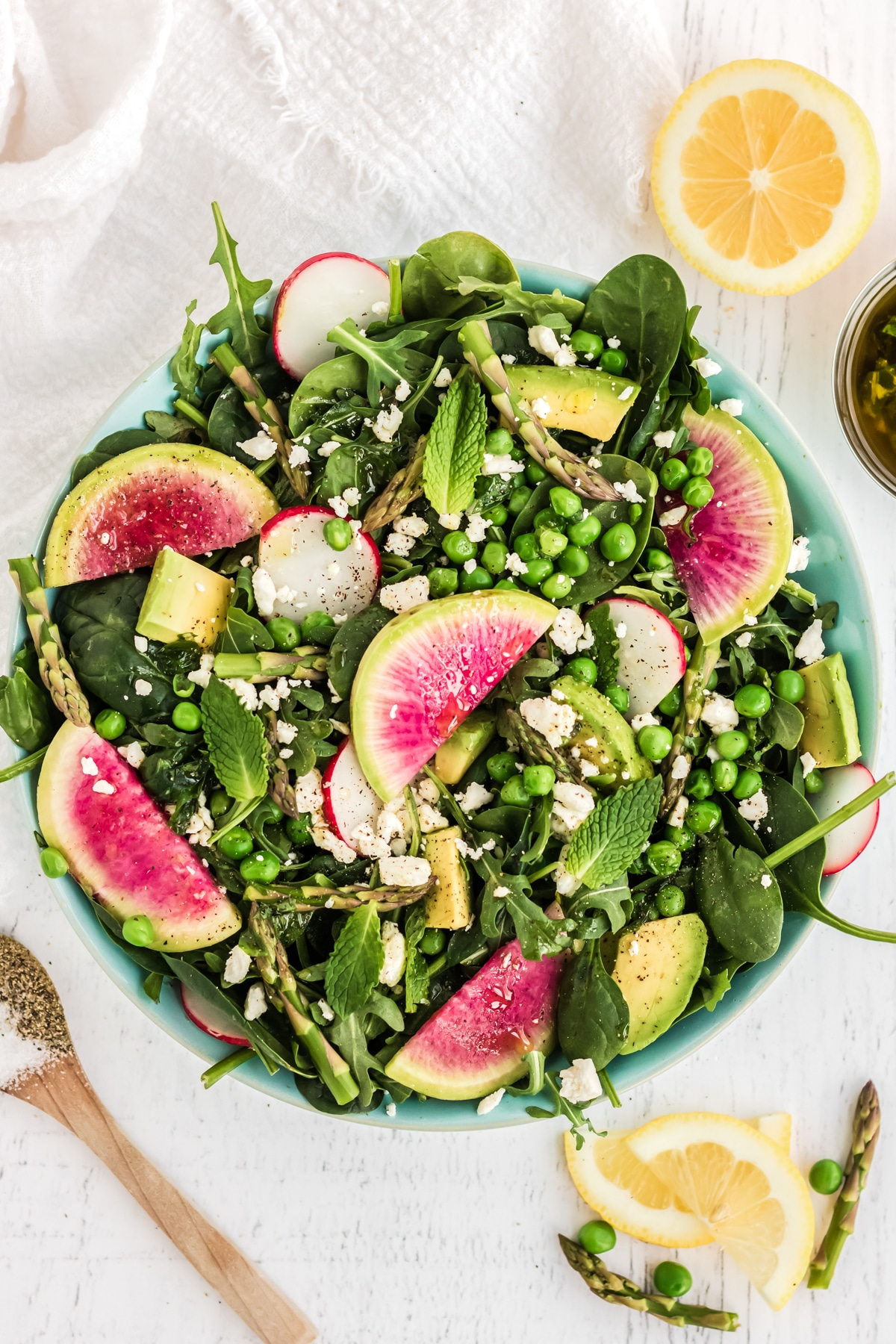 salad with peas, asparagus, watermelon radish, and feta cheese in a blue bowl on a white backgrop