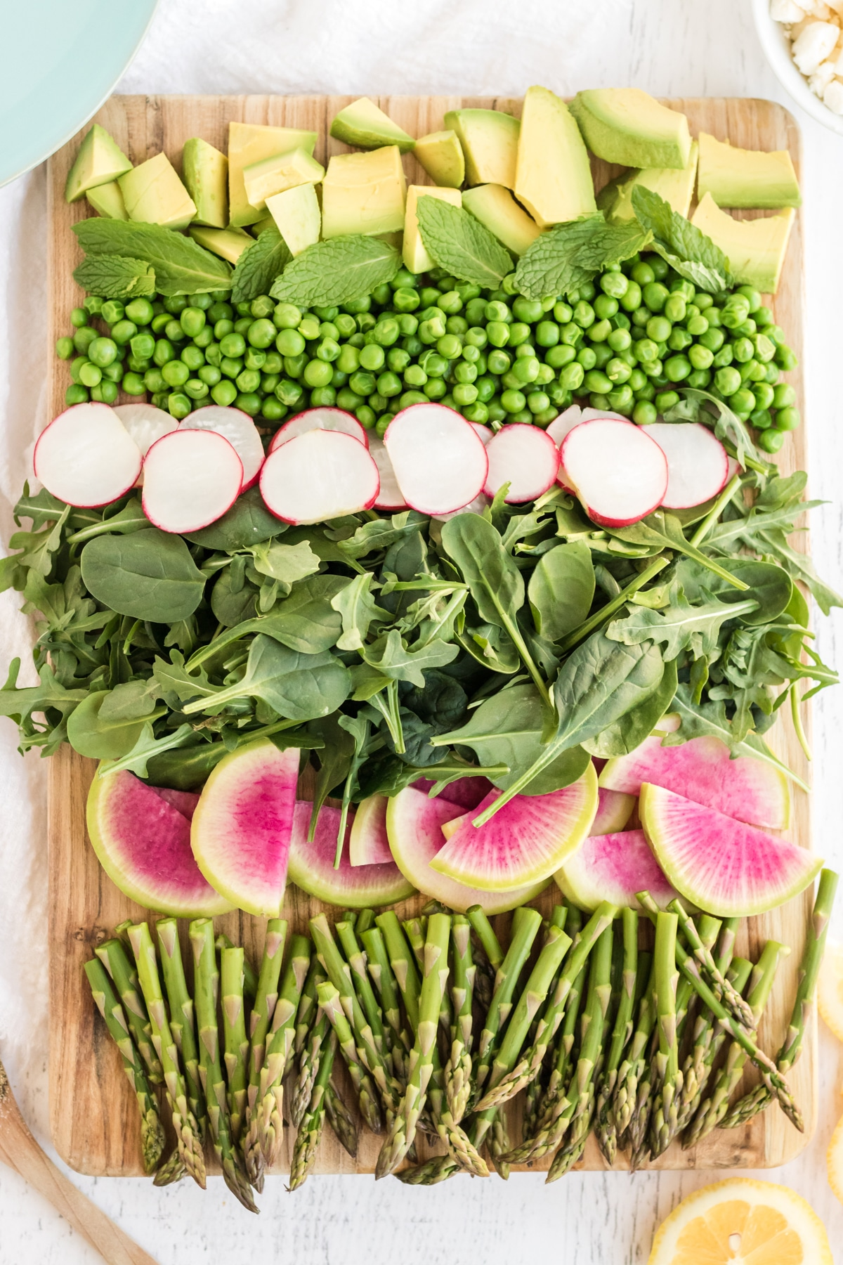 chopped avocado, mint leaves, peas, radishes, spring greens, watermelon radish, and asparagus lined up on a wooden cutting board