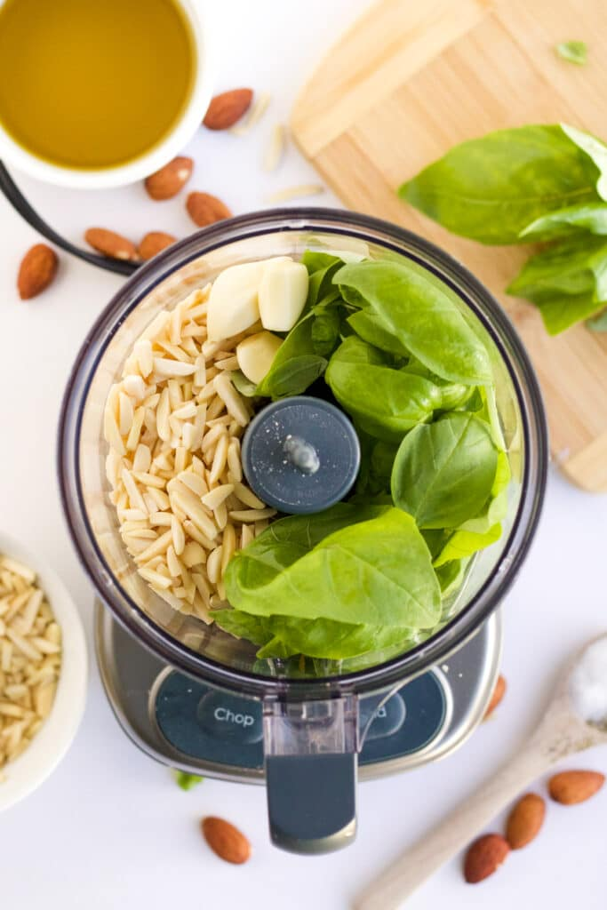 An overhead image of almond pesto being made. Slivered almonds, fresh basil, and garlic are combined in a food processor, preparing to be ground.