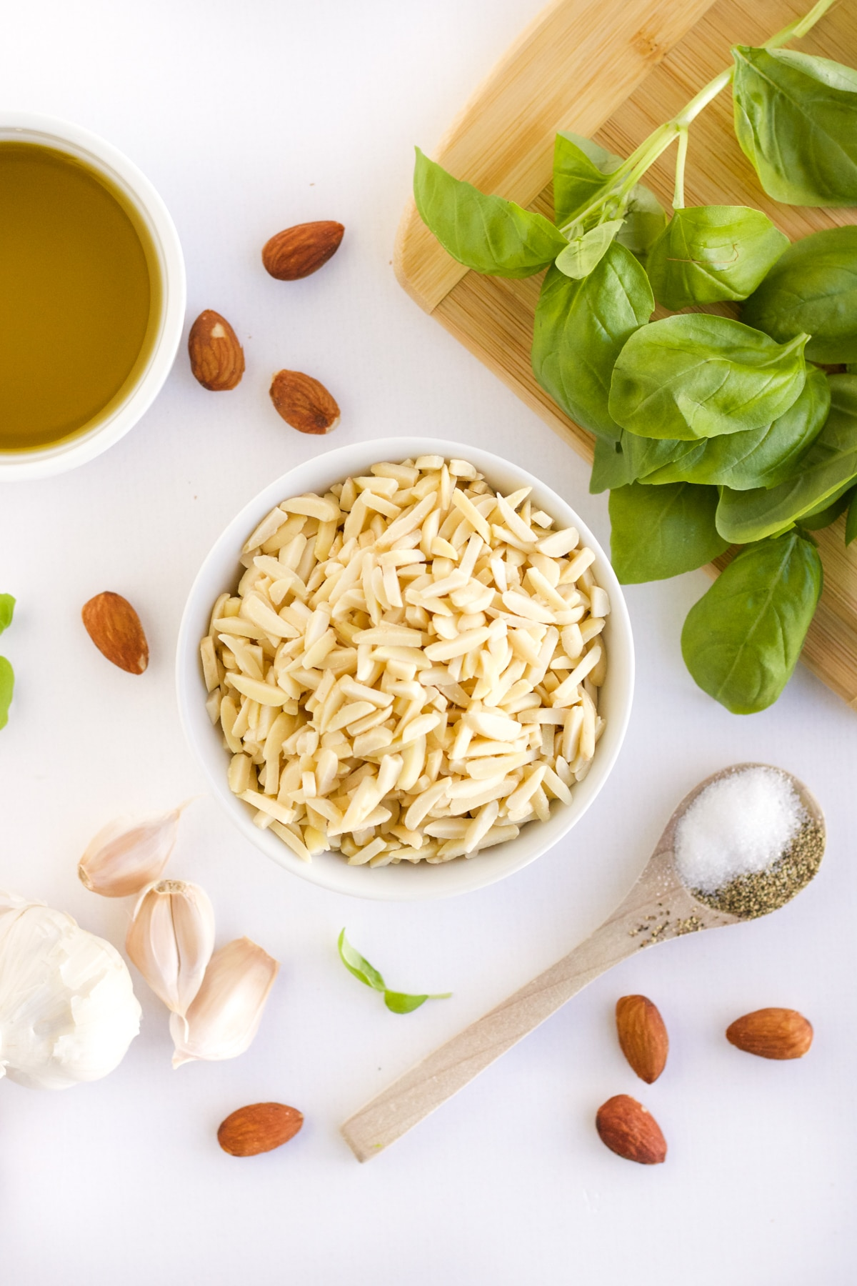 Ingredients for homemade almond pesto - slivered almonds, olive oil, fresh basil, garlic and salt and pepper