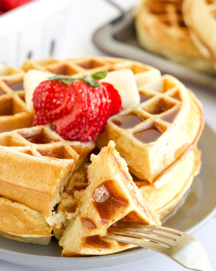 A stack of Belgium Waffles with a bite on a fork. The waffles are topped with strawberries, butter and syrup.