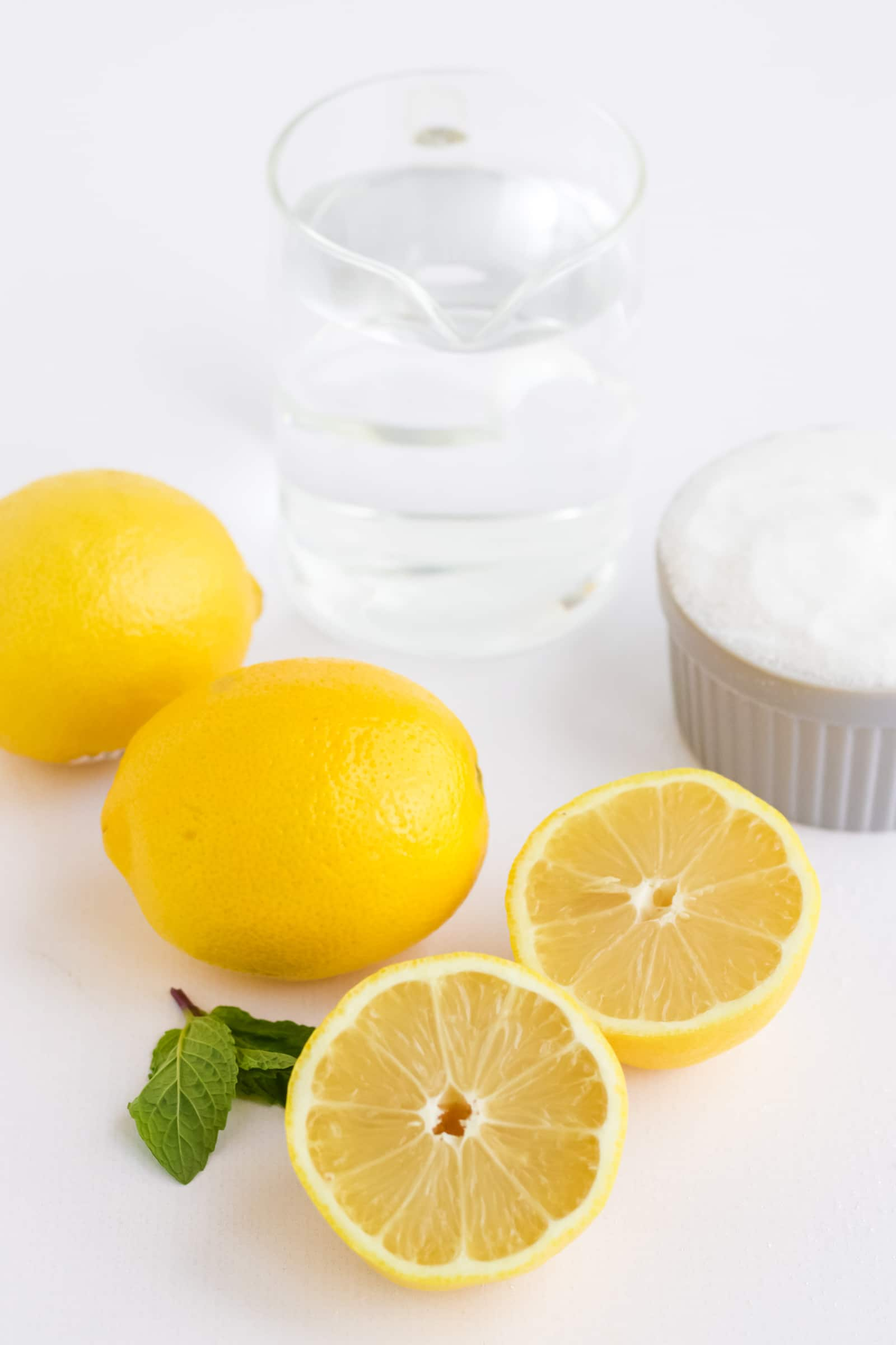 2 whole lemons 1 lemon sliced in half a pitcher of water and a bowl of sugar