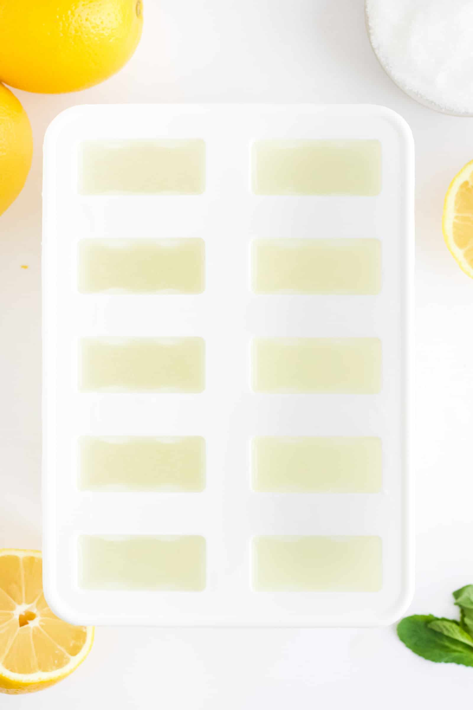 popsicle mold filled with lemonade and lemons and sugar in the background