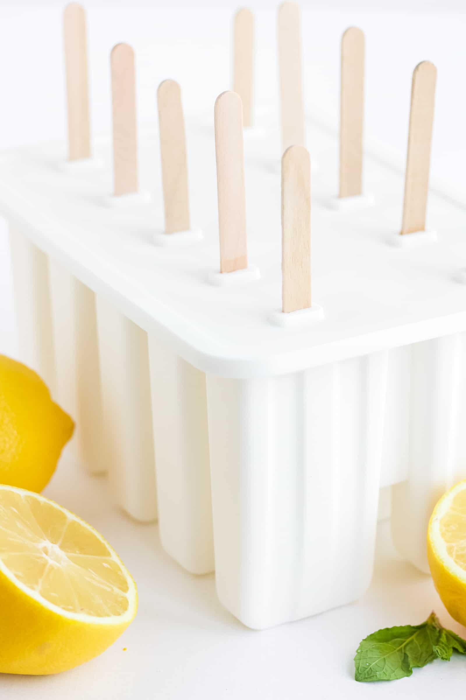 10 lemonade popsicles in a mold with cut lemons in the foreground