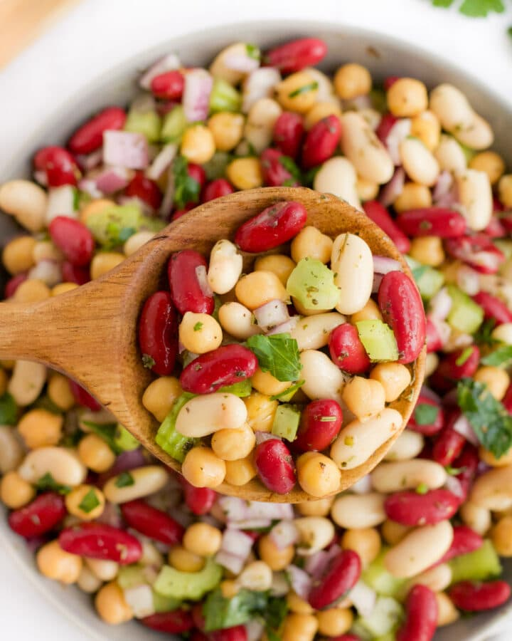 three bean salad being scooped by a wooden spoon